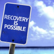 Recovery is Possible sign with a beach on background